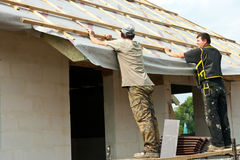 Homens que põr o telhado sobre uma casa   Fotografia de Stock Royalty Free