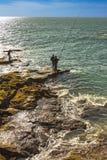 Homens que pescam fora das rochas de Paseo Fernando Quinones em Cadiz fotos de stock