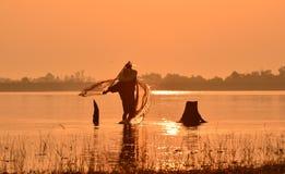 Homens que pescam na silhueta um barco de pesca Imagem de Stock