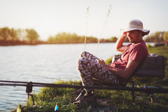 Homens que pescam no por do sol e que relaxam ao apreciar o passatempo Foto de Stock