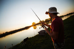 Homens que pescam no por do sol e que relaxam ao apreciar o passatempo Imagens de Stock