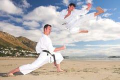 Homens que praticam o karaté na praia foto de stock royalty free