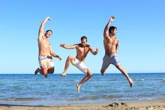 Homens que relaxam na praia Imagens de Stock