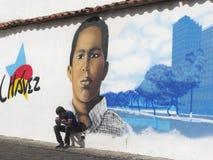 Homens que sentam-se em uma rua em Caracas com grafittis ex do presidente Hugo Chavez no fundo imagem de stock royalty free