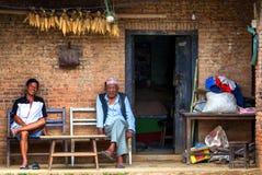Homens que sentam-se na frente da casa tradicional em Nepal imagens de stock