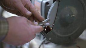 Homens que trabalham apontando a broca do metal em uma roda de moedura na fábrica industrial video estoque