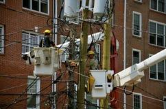 Homens que trabalham em polos da eletricidade Foto de Stock Royalty Free