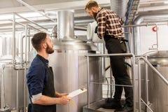 Homens que trabalham na cervejaria do ofício ou na planta da cerveja fotos de stock royalty free