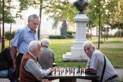 Homens superiores idosos que jogam a xadrez em um parque da fortaleza de Kalemegdan, em Belgrado, Sérvia fotografia de stock