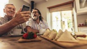 Homens superiores que fazem um bate-papo video no smartphone fotografia de stock royalty free
