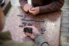 Homens superiores que jogam o dominó exterior fotografia de stock royalty free