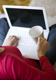 Homeoffice. Young woman is sitting on a couch at home and working with a laptop computer Royalty Free Stock Photo