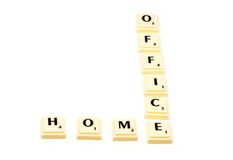 HOMEOFFICE. Conceptual approach using plastic letter tiles forming the two words home and office with shadows on white background Stock Images