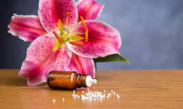 Homeopathic globules on wooden ground with lilly Stock Photos