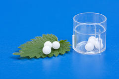 Homeopathic pills on Urtica Urens leaf Royalty Free Stock Images