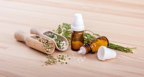 Homeopathic remedy of yarrow. Homeopathic remedy with flowering yarrow and two spoons with a wooden background Stock Image