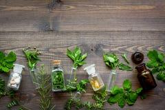 homeopathy Foglie delle erbe curative, delle bottiglie e delle pillole sul copyspace di legno di vista superiore del fondo Immagini Stock