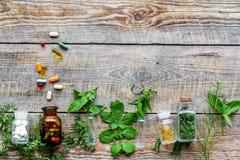 homeopathy Foglie delle erbe curative, delle bottiglie e delle pillole sul copyspace di legno di vista superiore del fondo Immagini Stock Libere da Diritti