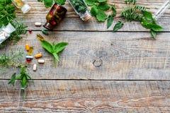 homeopathy Foglie delle erbe curative, delle bottiglie e delle pillole sul copyspace di legno di vista superiore del fondo Fotografie Stock
