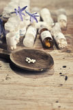 Homeopathy globules. Focus in homeopathy pills in wood  table Royalty Free Stock Photography