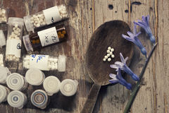Homeopathy globules in hand. Focus in homeopathy pills in wood spoon and table Stock Photo
