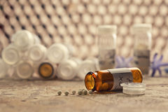 Homeopathy globules in hand. Focus in homeopathy pills in wood  table Royalty Free Stock Image