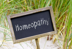 Homeopathy - wooden chalkboard with text. Alternative medicine royalty free stock image