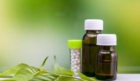 Homeopatii pojęcie – Trzy butelki homeopatii substancja na zielonym liściu z mieszanki żółtej zieleni tłem obrazy stock
