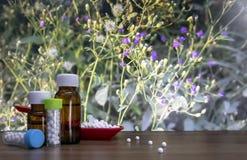 Homeopatyczne pigułki w czerwonej łyżce i butelce substancja z rozciągniętymi białymi sugarballs na drewnie ciecza i globula ukaz zdjęcie stock