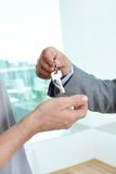 Homeowner. Real estate agent passing the key to the house to a satisfied male homeowner royalty free stock image
