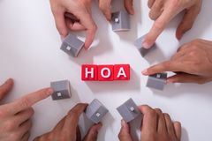 Homeowner Association Blocks. Surrounded By People Holding House Model On White Surface stock image