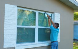 Homeowner caulking window weatherproofing home against rain and storms. Homeowner caulking window with a caulk gun, an important part of weatherproofing homes Royalty Free Stock Photos