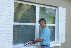 Homeowner caulking window weatherproofing home against rain water and storms. Homeowner caulking window with a caulk gun, an important part of weatherproofing Stock Images