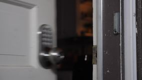 Homeowner enters passcode on door for entry. A homeowner enters a passcode on the door for entry stock video