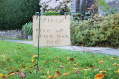Dog Waste and Homemade English Sign. A homeowner has posted a small, simple sign in English asking owners to clean up after their dog Royalty Free Stock Photo