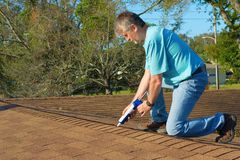 Homeowner patching roof with caulk gun protection from rain storms. Homeowner patching roof with roof repair tar in caulk gun doing home maintenance to protect Stock Photo