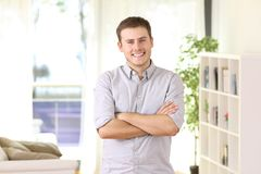 Homeowner portrait posing at home. Happy homeowner portrait posing standing at home with furniture and window in the background Stock Image