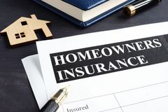 Homeowners insurance policy and model of home. royalty free stock image