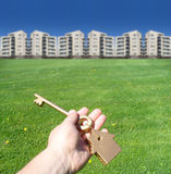 Homeownership concept. A concept for homeownership. A hand holding a key to a house with buildings in the background Royalty Free Stock Image