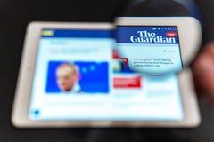 Homepage do Web site da not?cia de The Guardian na tela da tabuleta Logotipo do canal de not?cias do guardi?o imagens de stock royalty free