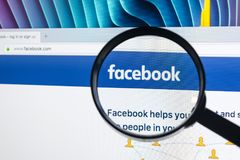 Homepage of Facebook.com on Apple iMac monitor screen under magnifying glass. Stock Photography