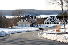 Homes. Winter view of a nice neighborhood with a view of a frozen lake in the background Royalty Free Stock Photo