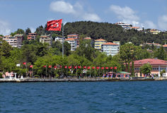 Homes along and turkish flag the Bosporus Turkey. Homes along and turkish flag the Bosporus istanbul Turkey royalty free stock photo