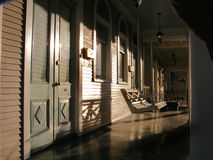 Homes-Front Porch Swing at Sunset. Front Porch in Warm Sunset Light:  As an Illustration Photograph to indicate Home, Another Time, Comfort, Security, and a Royalty Free Stock Images