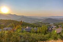 Homes on a hill in Park City Utah at sunset. Aerial view of homes amid lush trees on a hill in Park City, Utah at sunset. The bright setting sun cast a golden stock photography