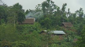 Homes and Huts in Forest Terrain. Steady, medium wide shot of homes in forest terrain stock video footage