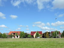 Homes, meadow and cloudy sky Stock Image