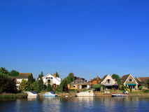 Homes and moored boats on the River Thames. At Windsor on a tranquil sunny day with plenty of copy space Stock Photo