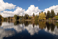Homes on the RiverMirror Pond, Bend. Mirror pond in downtown Bend is almost perfectly still in this autumnal image of peace. Located on the Deschutes River it Royalty Free Stock Photo