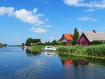 Homes and ships in river Minija in summer, Lithuania Royalty Free Stock Image